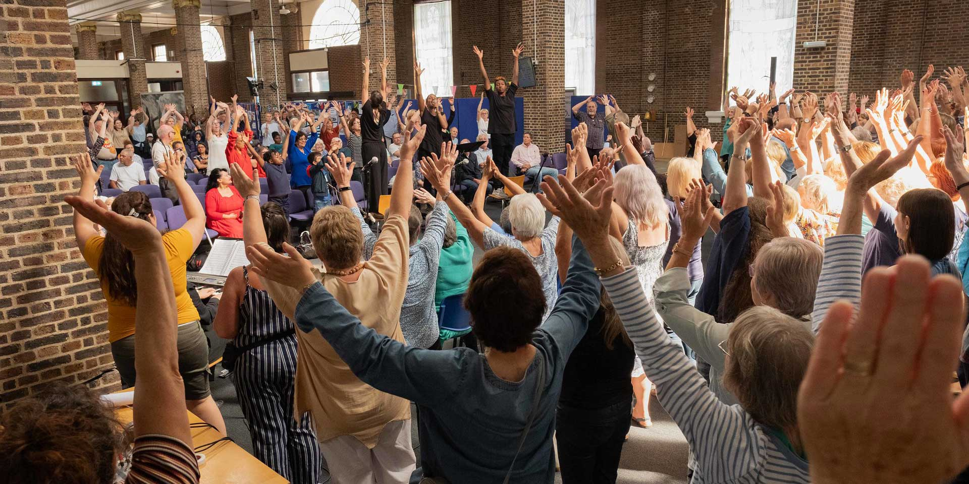 Community group cheering with hands in the air